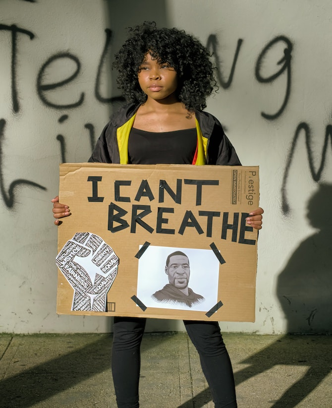 Black woman holding a I can't breathe sign