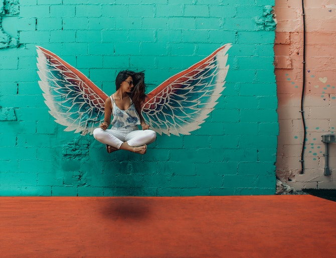 Woman sitting in front of a wall with wings